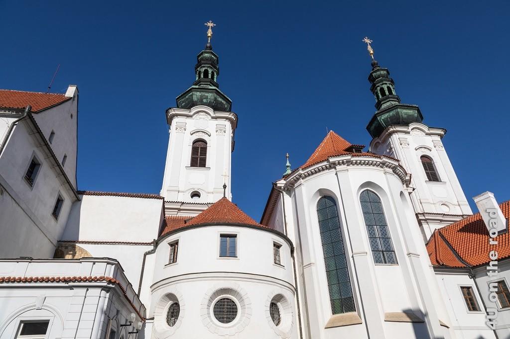 Bild Kloster Strahov Kirche, Prag zeigt den Sakralbau aus dem Innenhof fotografiert mit seinen Türmen und Seitenschiffen. Der Kontrast zwischen blauem Himmel, weisser Kirche mit roten Dächern und Kupfernen Türmen ist wunderschön.