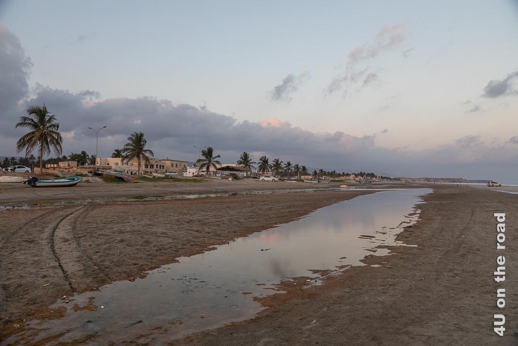 Bild Strand bei Taqua im Abendlicht zeigt einen endlosen Sandstrand, der zur Strasse von einzelnen Palmen abgegrenzt wird. Boote stehen auf dem Trockenen, Autos stehen in Fahrtrichtung Meer auf dem Sand. Ein langer Fluss ist von der letzten Flut am Strand zurückgeblieben.