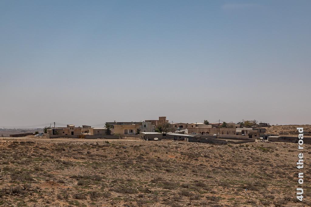 Bild kleinere und mittlere Ortschaften bevölkern das Hochplateau zeigt eine kleine Ortschaft mit maximal 2-geschossigen, ummauerten Häusern in karger Landschaft. Einzelne grüne Büschel wachsen auf dem felsigen Boden.