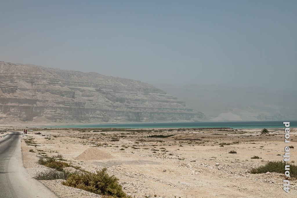 Bild Die Sichtweite sinkt zeigt massive ausgewaschene Sandsteinfelsen, die die gegenüber liegende Bucht begrenzen und das grün-türkise Meer.