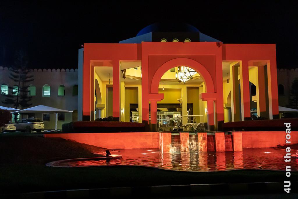 Bild Hotel in Mirbat in der Dunkelheit erleuchtet zeigt die Wasserspiele und das Hotel Portal in rotem Licht angeleuchtet in der Dunkelheit.