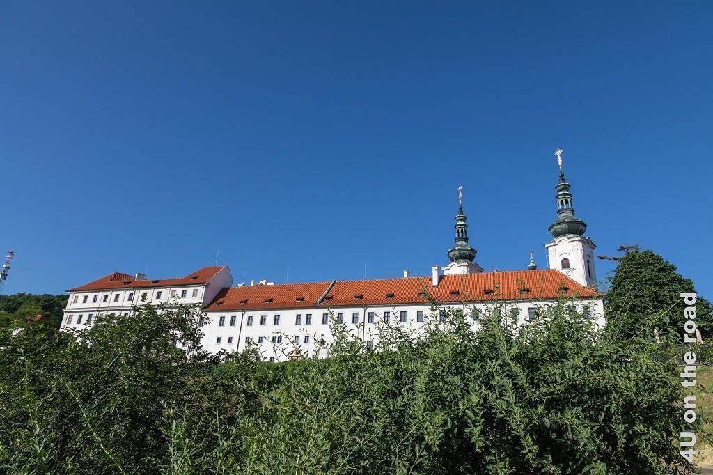 Bild Kloster Strahov, Prag von unten gesehen, zeigt das Kloster von den unterhalb befindlichen Gärten aus fotografiert. Es reckt sich mit seiner weissen Fassade, dem roten Dach und den Kupfernen Türmen kontrastreich in den makellos blauen Himmel.