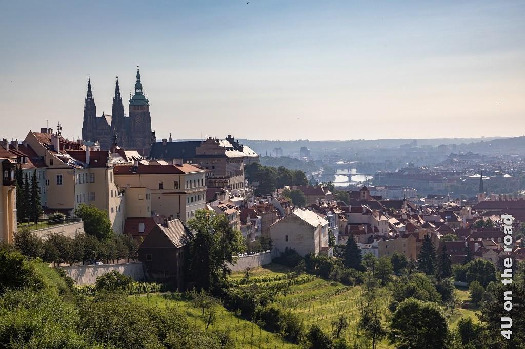 Bild Blick auf die Burganlage vom Kloster Strahov, Prag zeigt im Vordergrund die Gärten hinter denen sich dann die Burganlage erhebt. Die Moldau und die Häuser rechts und links des Flusses liegen im Morgendunst.