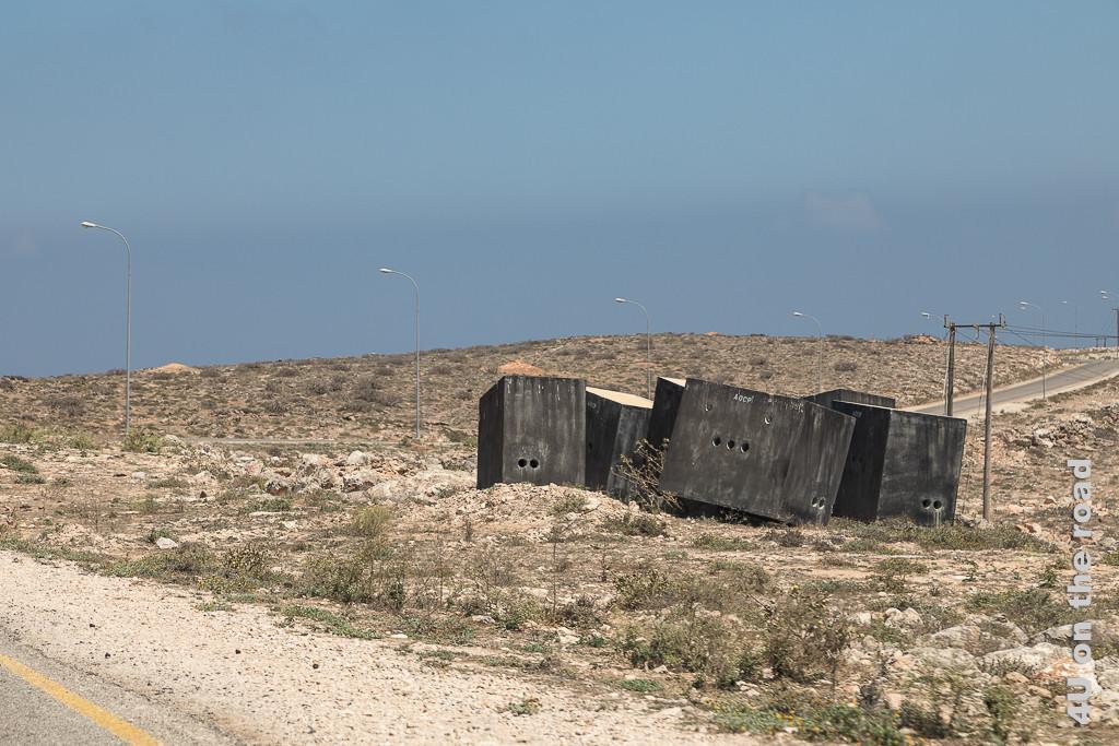 Bild Gefechtsstände am Strassenrand zeigt sechs verschachtelte schwarze Beton Rechtecke mit Schiessscharten mitten in der steinigen Landschaft