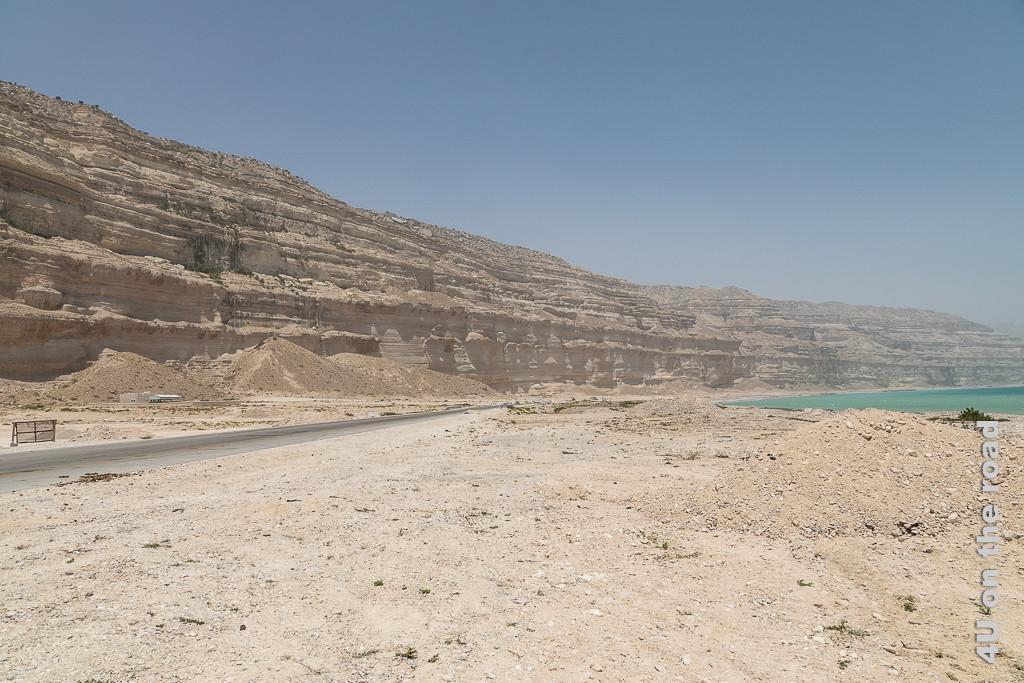 Bild vom Winde verwittert zeigt Windersosion an den Sandsteinklippen der Küste, daneben das türkisfarbene Meer