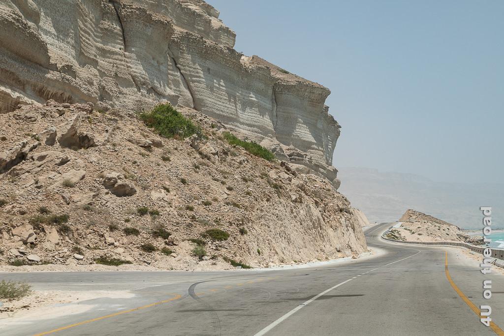 Bild Der Wind und die Staubpartikel in der Luft nehmen zu zeigt am Fuss stark verwitterte Sandsteinfelsen durch die sich die Strasse windet. Der Hintergrund ist im Dunst nur noch zu erahnen.