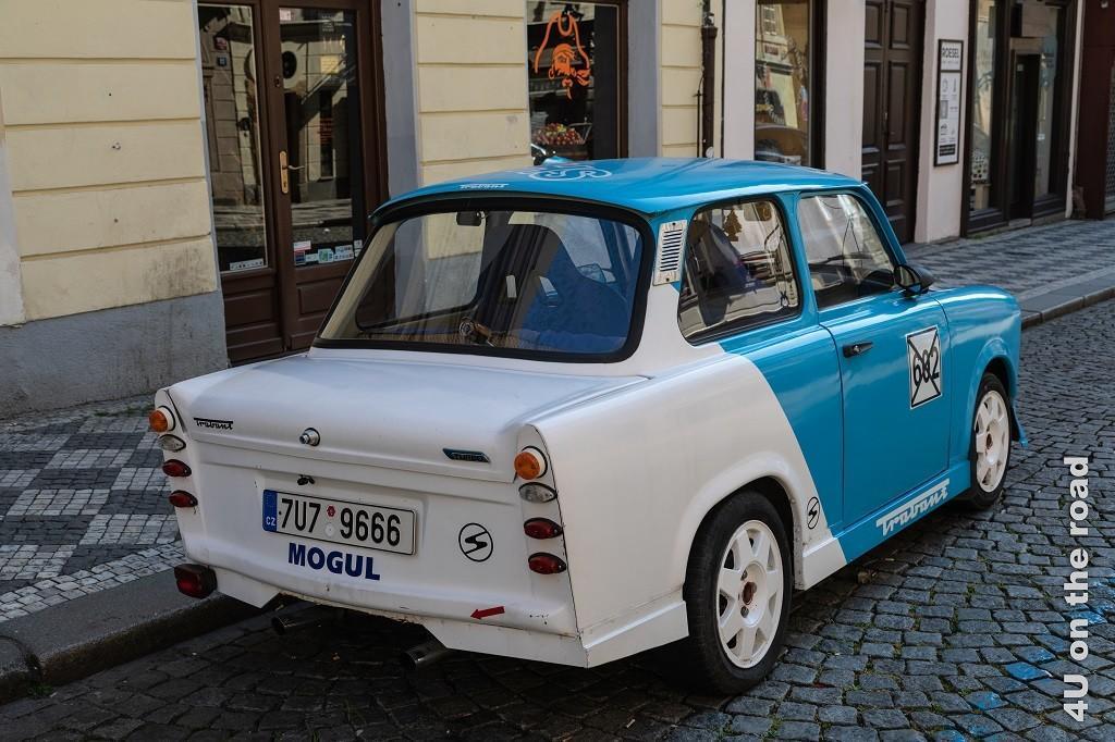 Bild Trabant, Prag zeigt einen vorne hellblauen, hinten weissen sehr alten Trabant. Den Rücklichtern nach aus den 60er Jahren. Der Trabi hat noch die Strassenverkehrszulassung.