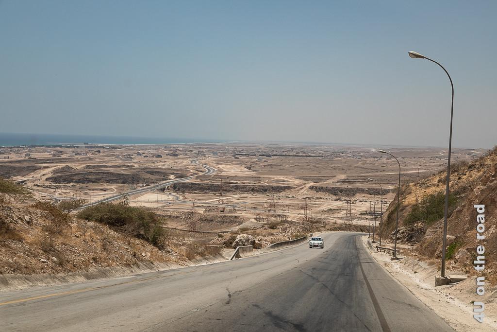 Auf dem Weg nach Salalah - Blick von oben auf die trockene Küste zeigt die sich zum Meer windende Strasse mit Laternen und Strommasten. Kein Grün erfreut das Auge