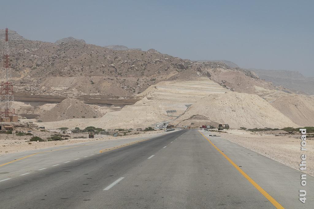 Bild Kontrollposten in der Ferne zeigt die sich in die Berge windende Küstenstrasse, davor ein Kontrollposten mit Strassensperre, Militärfahrzeugen und Sonnenschutzzelt.