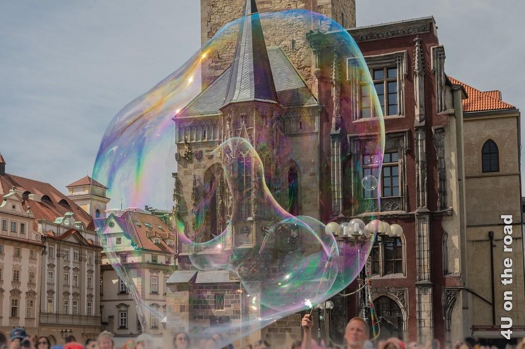 Bild Rathaus Prag hinter Seifenblase zeigt eine gigantische Seifenblase, durch die verschwommen das Rathaus zu sehen ist.