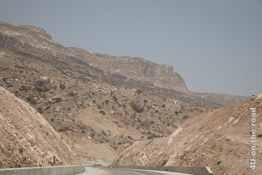 Bild Felsbrocken in Absturzposition zeigt verfestigte Sandsteinfelsen mit grossem Schüttkegel auf dem grosse Felsbrocken liegen, die sich bei der kleinsten Erschütterung wahrscheinlich auf den Weg machen, um in Richtung Strasse zu rutschen.