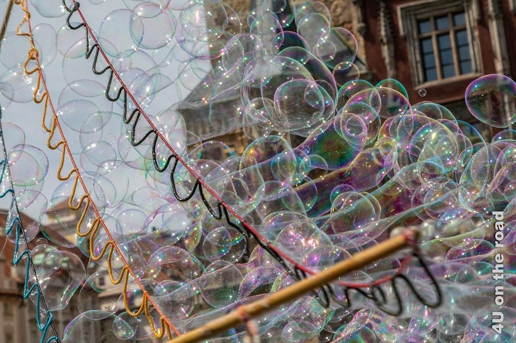 Bild Seifenblasen, Prag zeigen einen Stab mit drei nebeneinander verlaufenden Schlaufen, durch welche zahlreiche Seifenblasen generiert werden.
