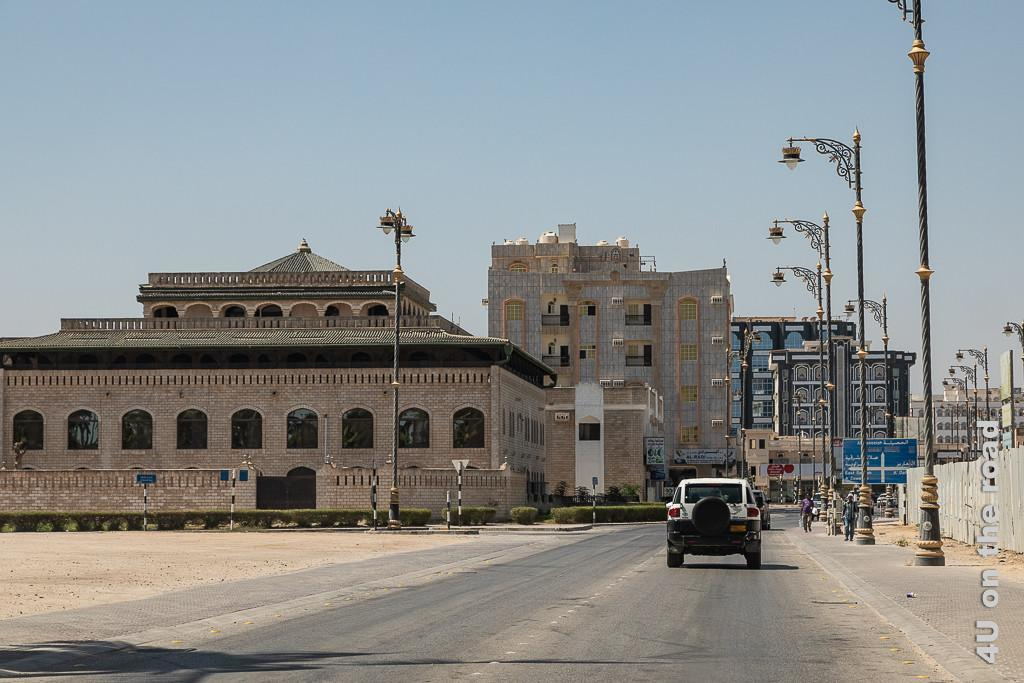 Bild Salalah Stadt Impressionen zeigt arabische Stadtarchitektur und prunkvolle Laternen entlang der Strasse
