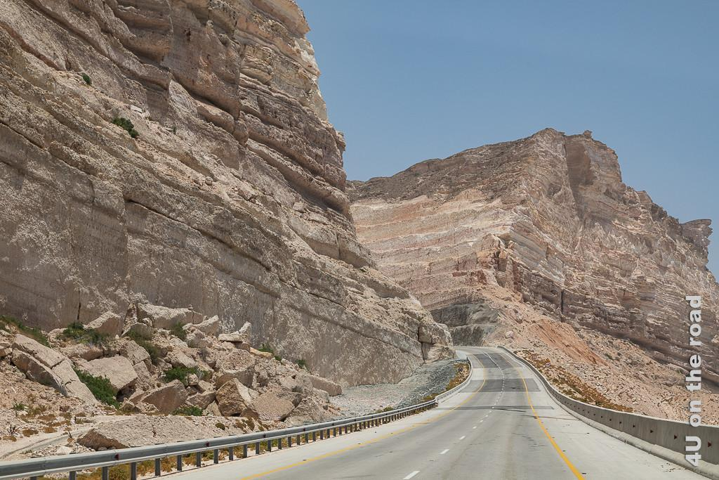 Bild Strassenbau mit tiefen Einschnitten in den Berg zeigt den Strassenverlauf in die Berge. Man sieht allein 8 in den Berg gearbeitete Terrassen, wobei die unteren mit Beton überzogen sind.