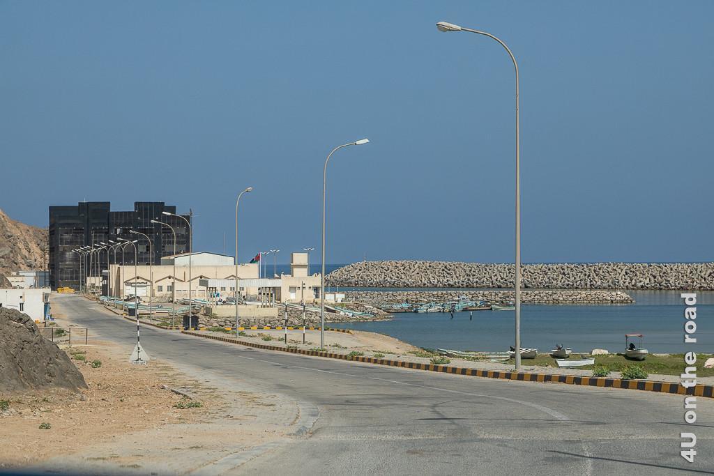 Bild Dhalkut, Oman - Hafen und Fischfabrik zeigt kleine Boote im Hafen, die hohe Hafenmauer und das dunkelbraune, gläserne Fabrikgebäude.