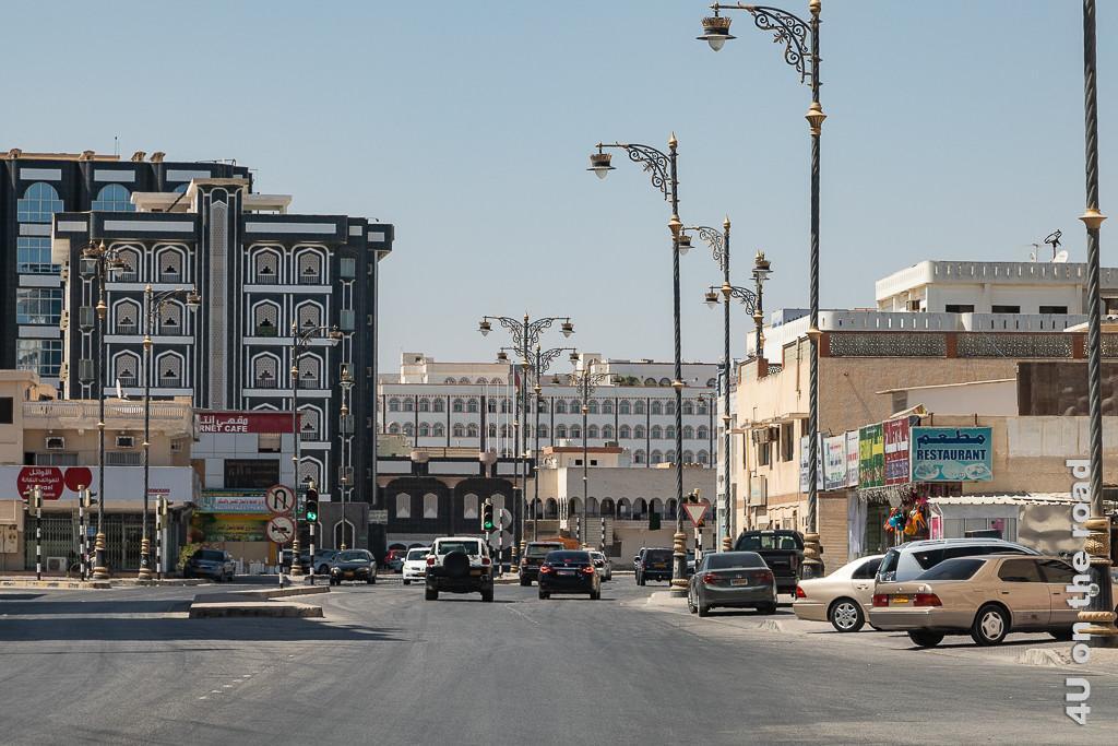 Bild Salalah Stadt Impressionen zeigt arabische Stadtarchitektur, prunkvolle Laternen und Werbeschilder entlang der Strasse