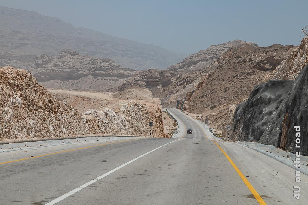 Bild Strasse durch die Felswüste zeigt die Felsen in der Mitte die Strasse aus der Sicht verschwindet.