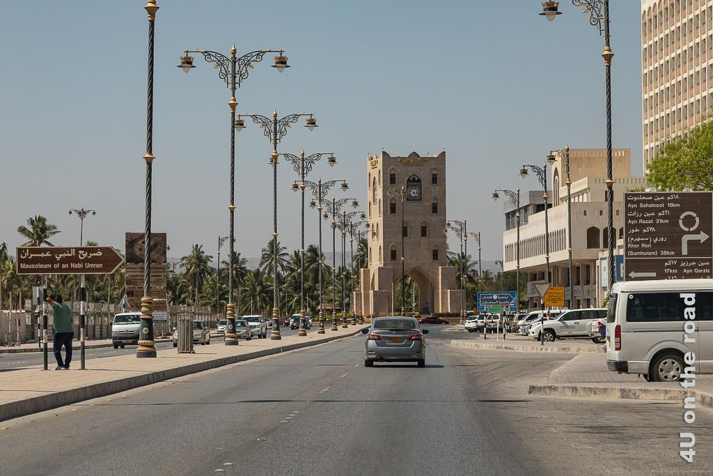 Bild Salalah Stadt Impressionen zeigt den Kreisel mit Uhrturm, prunkvolle Laternen, Autos und Palmen