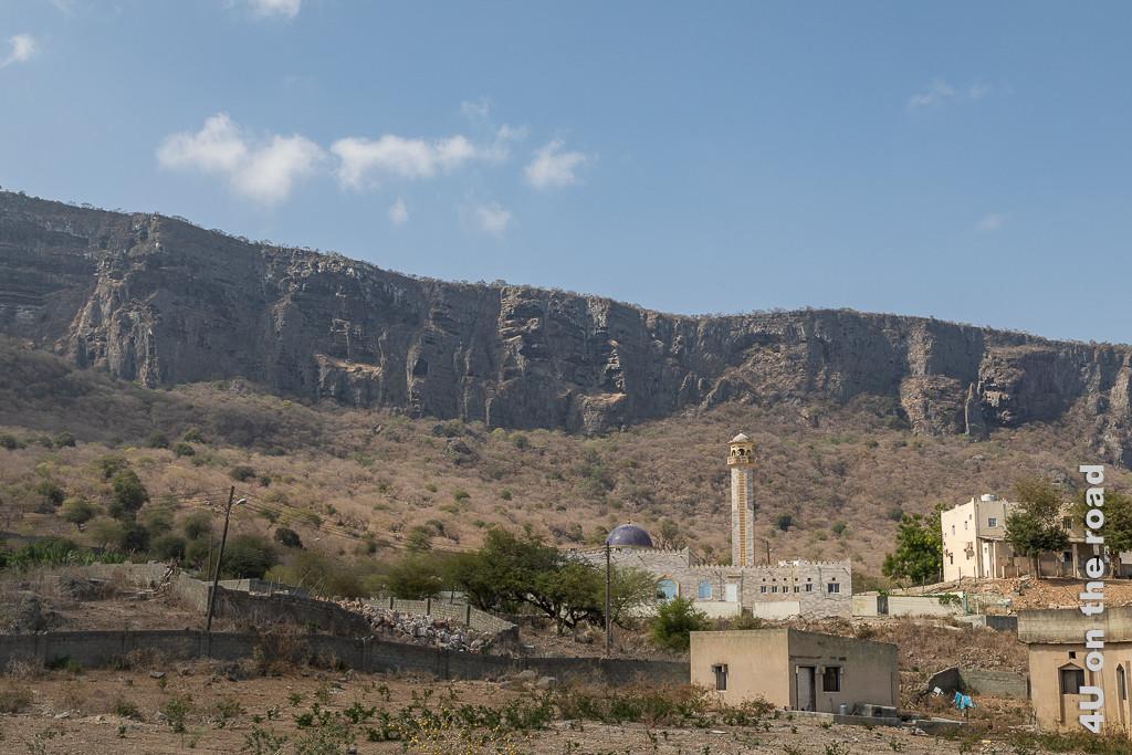 Bild Schroff erheben sich die Felsen hinter dem kleinen Ort empor zeigt eine aus Steinen gemauerte Moschee mit lila Kuppel, Ställe und ein Wohnhaus. An den sanften Hängen unterhalb der Felsen wachsen Bäume und Büsche, die teilweise grün sind.