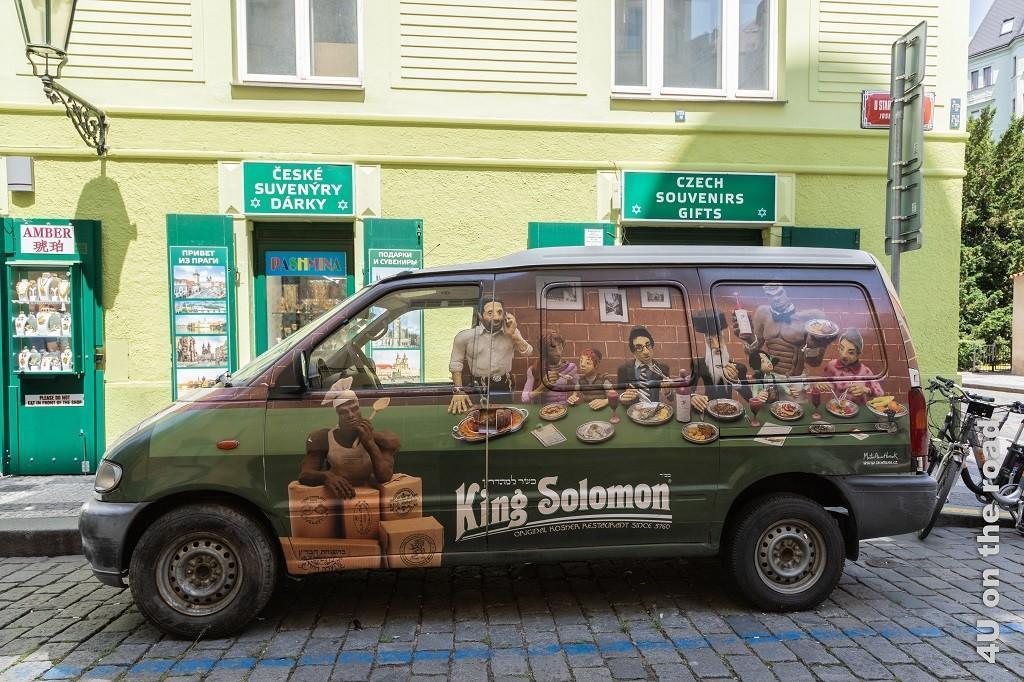Bild Restaurantwerbung im jüdischen Viertel, Prag zeigt einen Van mit Personen an einer langen Tafel, die von muskulösen dunkelhäutigen Kellnern bedient werden. Die Werbung ist für King Solomons koscheres Essen.