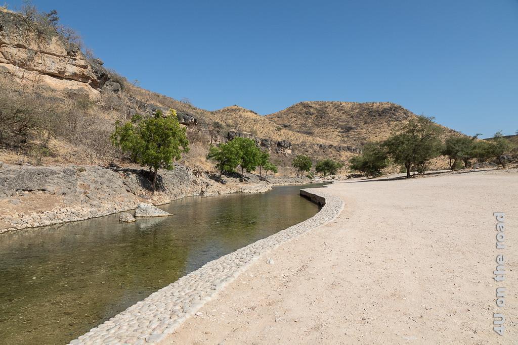 Bild Ain Razat - gefasster Flusslauf zeigt die Hänge aus denen das Wasser kommt, Bäume am felsigen Ufer und das flache Ufer an dem gepicknickt werden kann.