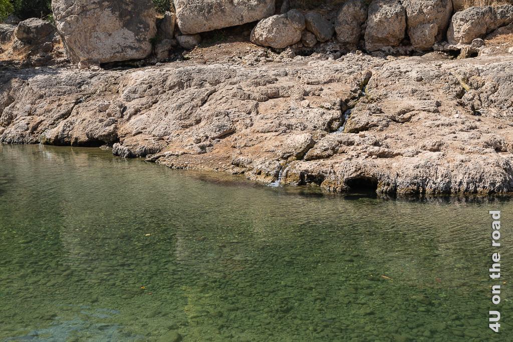 Bild ein kleines Rinnsal kommt aus dem Berg geflossen zeigt den flachen Fluss und das felsige Ufer. Aus den Felsen kommt Wasser geflossen.