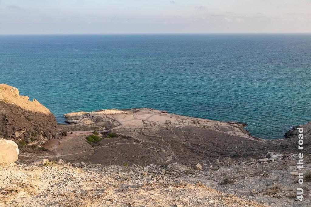 Bild Blick von oben auf das Gelände der Blowholes, Oman lässt die Wege und Picknick Plätze und Absperrungen erkennen. Das Meer hat eine türkis-blaue Farbe