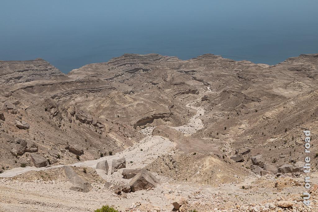 Blick von oben auf ein Trockenes Flussbett in der Felswüste zeigt das sich durch die Felsen tief eingegrabene Flussbett auf seinem Weg zum Meer