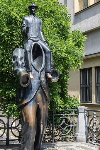Bild Skulptur Kopfloser Mann auf dessen Schultern Franz Kafka sitzt - Franz Kafka Denkmal, Prag ist ein Denkmal am Geburtshaus von Franz Kafka