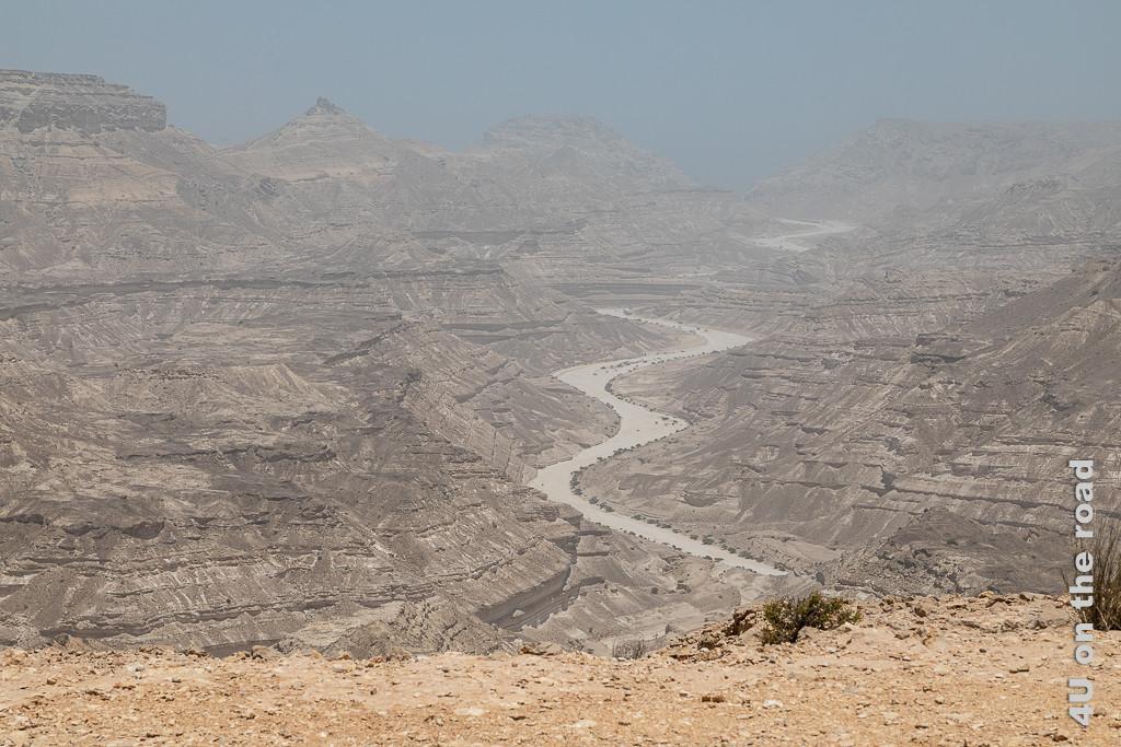 Bild Trockenes Flussbett mit grünen Büschen am Rand zeigt ein feinsandiges Flussbett, welches sich in gleichmässigen Kurven zum Meer windet. Die Felsen haben quergestreifte Erosionen.