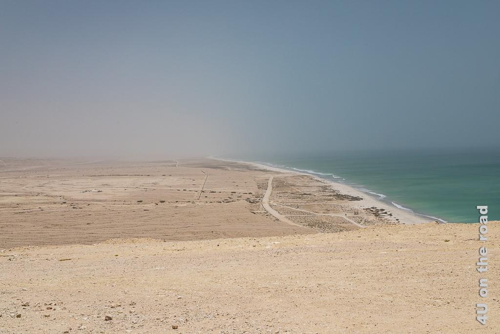 Bild Einsamer Sandstrand soweit das Auge sieht zeigt von oben das Meer mit einem schmalen ewig langen Sandstrand und die Wüste. Vom Landesinneren kommen Staubwolken zum Meer.