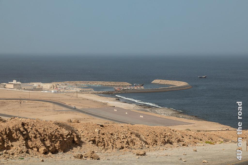 Kleiner Hafen vor Al-Lakbi zeigt von oben den von einer Mauer geschützten Hafen mit Daus und kleinen Motorbooten.