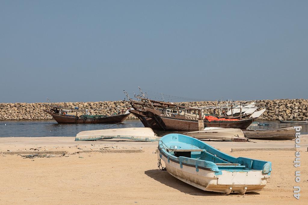 Bild Schiffe im Hafen von Al-Lakbi zeigt im Vordergrund ein blau-weisses Boot ohne Motor, nebeneinander liegennde braune Daus und ein einfahrendes Dau.
