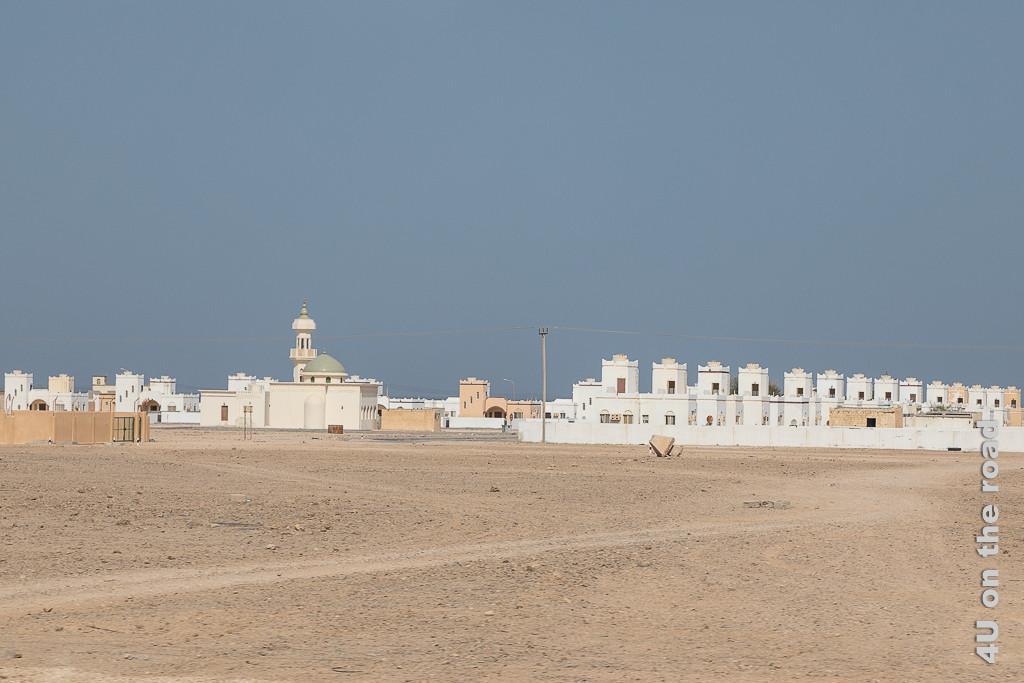 Bild Reihenhäuser in Al-Lakbi zeigeneher untypische Reihenhäuser, die eine Art Turm auf der unteren Etage aufgebaut haben, die Moschee und weitere Häuser sind auch zu sehen. Es gibt hier nicht die kleinste Grünpflanze zu sehen.