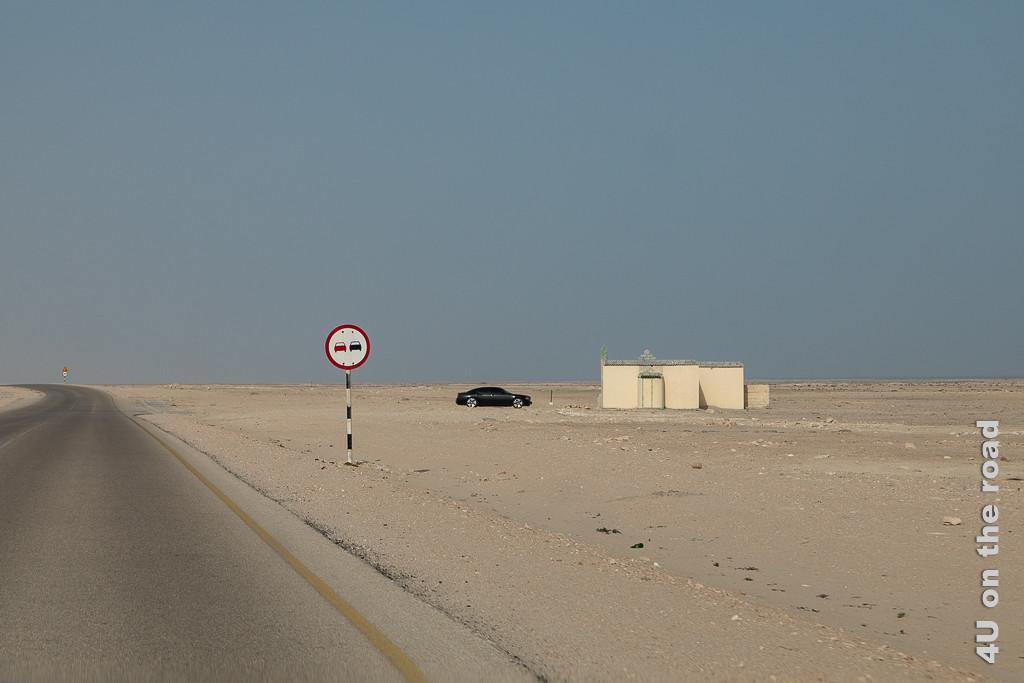 Bild Ob das ein Wohnhaus ist? zeigt an einem Überholverbotsschild einsam in der Landschaft stehendes Minihaus mit Wassertank und einem schwarzen PKW davor.