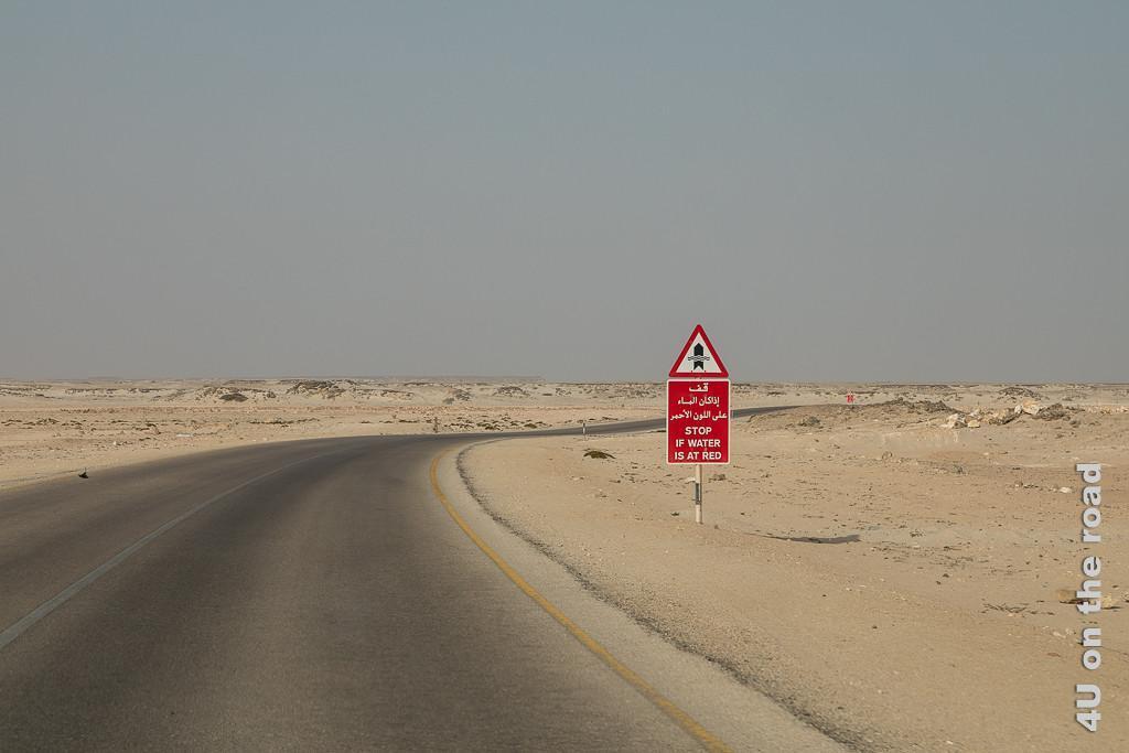Bild Manchmal scheint es auch hier zu regnen zeigt inmitten der Sandwüste rote Warnschilder mit Wasserstandsmesser und der Aufforderung anzuhalten, wenn das Wasser das rote Schild erreicht hat.
