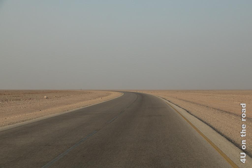 Bild Das Nichts zeigt die Strasse, welche durch eine Ebene mit kleinen Steinchen und Sand führt. Die Ebene reicht so weit das Auge blickt.