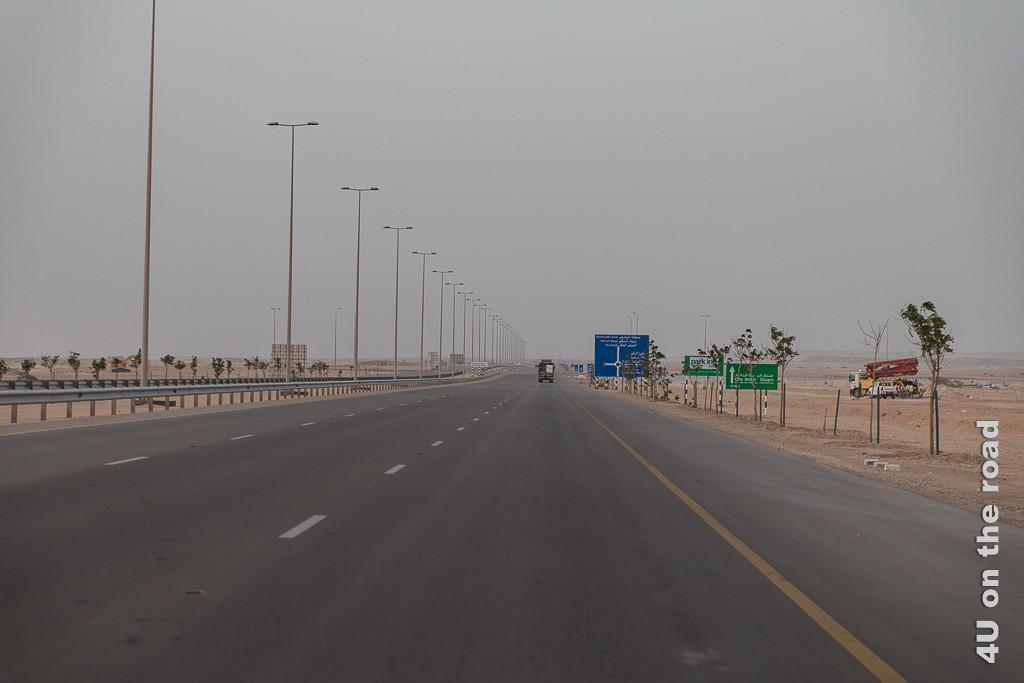 Bild Breite Strassen führen nach Duqm zeigt eine zwei Mal 3-spurige Strasse mit Standspur und Mittelstreifen mit Laternen, auf der nur ein Auto unterwegs ist.