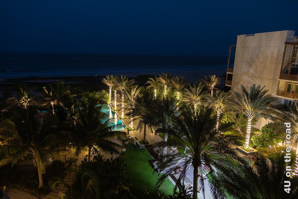 Bild Blick vom Balkon des Hotels in Duqm zeigt den mit Palmen bepflanzten, beleuchteten Innenhof des Hotels. Der Pool leuchtet türkis. Das Meer kann man ahnen.
