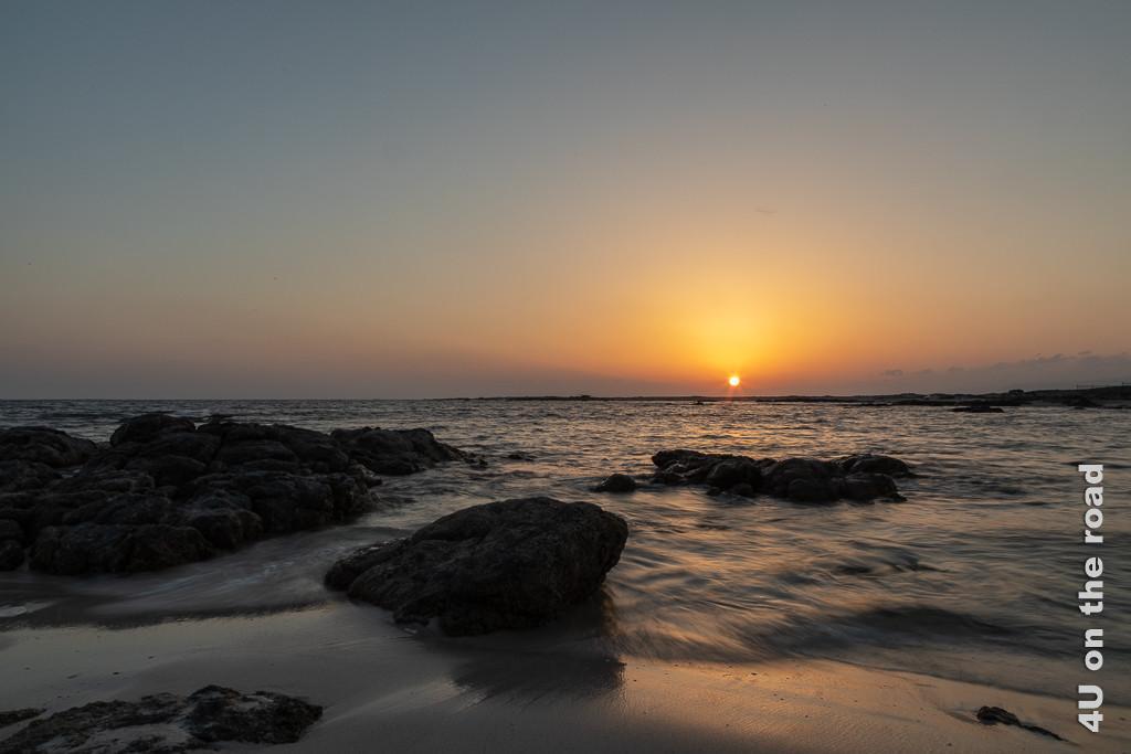 Bild Sonnenuntergang am Strand in Mirbat zeigt vom Meerwasser umspülte Felsen und die fast im Meer versinkende Sonne.