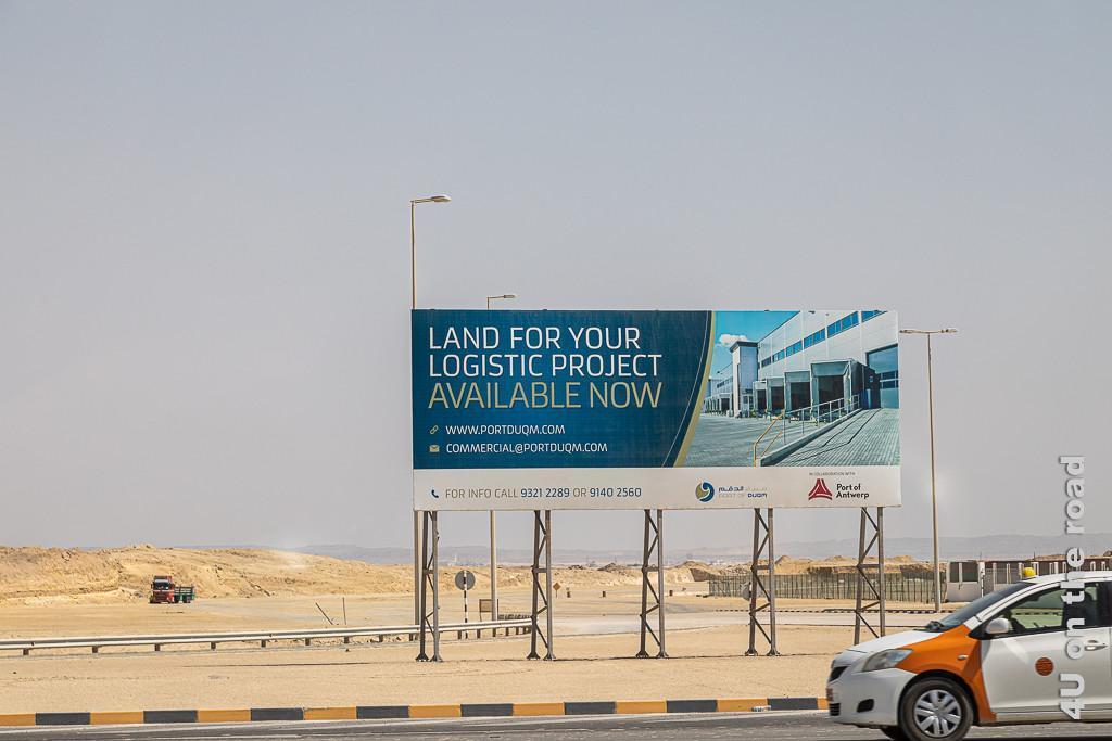 Bild Werbung am Strassenrand für Bauland in Duqm zeigt ein Schild scheinbar in der Wüste stehend, durch die ein LKW fährt. Vor dem Schild braust ein Taxi in den Farben weiss-orange entlang.