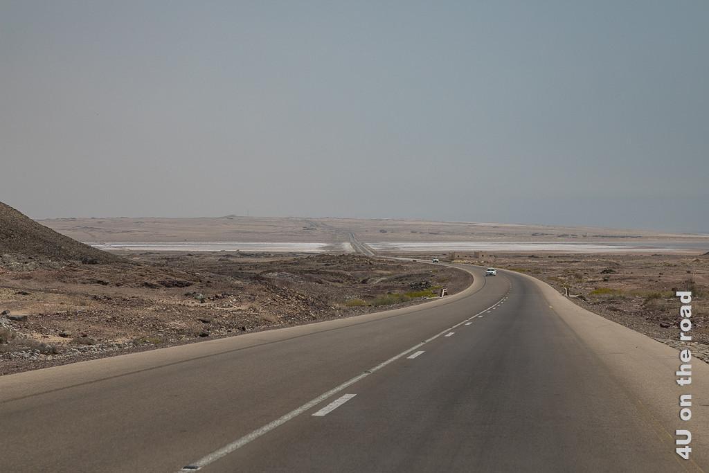 Salzsee aus der Ferne - Bild zeigt einen breiten Dip im Strassenverlauf. Rechts und Links der Strasse schimmert weiss das Salz in der ansonsten felsigen und sandigen Landschaft.