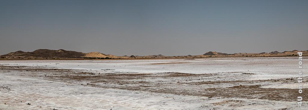 Bild Panorama Salzsee zeigt den salzverkrusteten Boden. Im Hintergrund der Pfanne erheben sich Dünen.