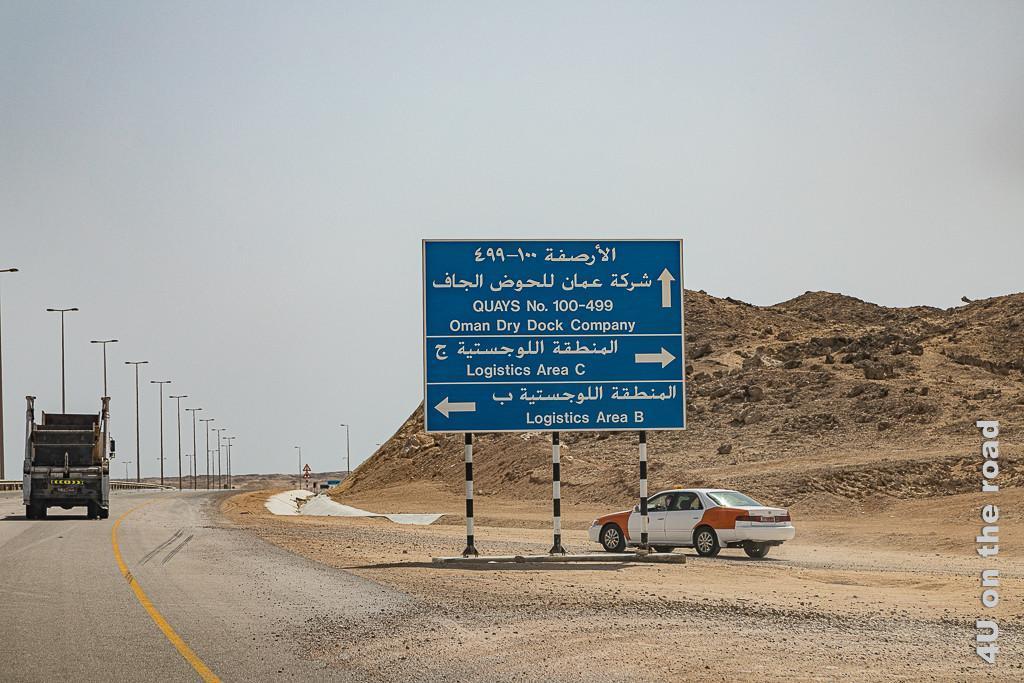 Hinweisschild zum Hafen von Duqm gibt schon einmal eine Vorstellung von der Grösse des Hafens. Auf dem Hinweisschild sind die Quais 100 bis 499 und die Logistik Gebiete A und B ausgeschildert. Ein Taxi schiesst hinter dem Schild auf die Strasse zu.