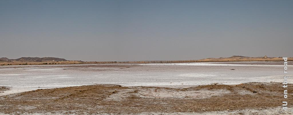Bild Panorama 2 Salzsee zeigt die Verlängerung von Panorama eins. Man kann das Meer ahnen. Es verschmilzt mit dem Horizont. Rechts und links erheben sich Felsen bzw. Dünen.