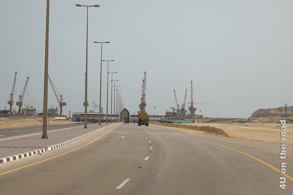 Bild Hafen von Duqm - Eingangskontrolle zeigt im Vordergrund die Ein- und Ausgangskontrolle mit einem Haus in der Mitte und im Hintergrund sieht man grosse Schiffe liegen und sieht die Hafenkräne.