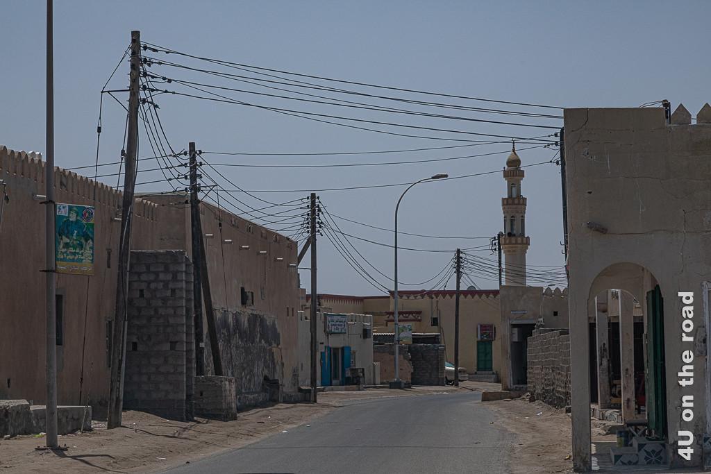 Bild Traditionelle, einfache Bauweise zeigt Häuser, wie aussehend wie Burgen zur Strassenseite, ordentlich verdrahtete Strommasten und den Turm einer Moschee.