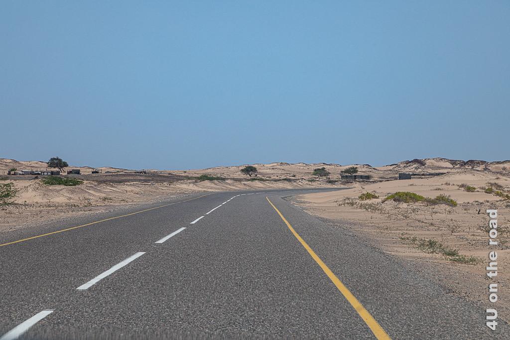 BIld Strasse im Meer aus Sand zeigt höher werdende Dünen rechts und links neben der Strasse. Durch den Fahrtwind der Autos sieht der Sand aus, als wäre er auf die Dünen gekehrt worden.