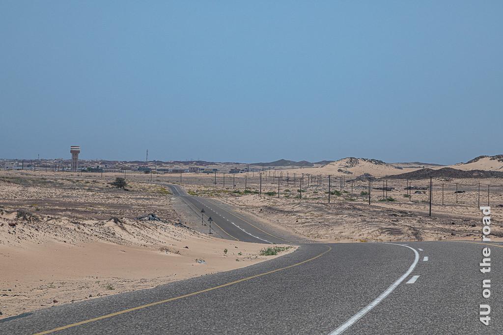 Bild Stadt im Sand zeigt viele Stromleitungen und hohe Dünen, die zu einem grösseren Ort mit Wasserturm führen.