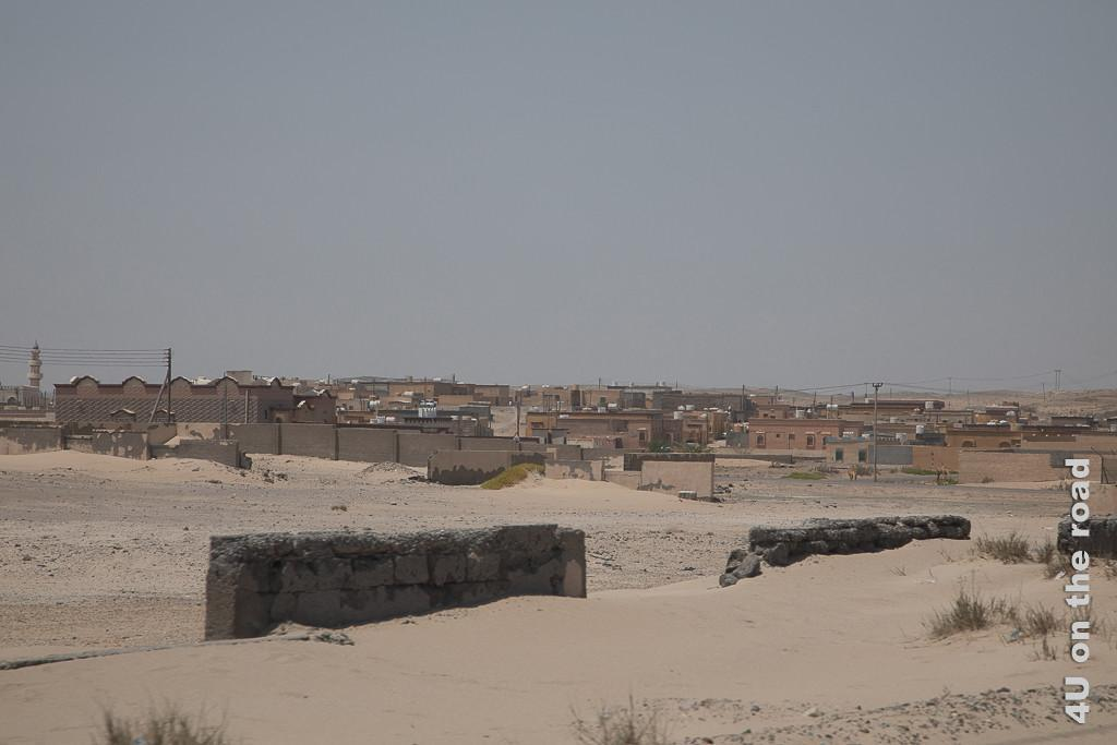 Bild Ort im Sand zeigt einen kleinen Ort, dessen Einwohner mit Hilfe von Mauern versuchen den Sand von ihren Häusern fernzuhalten. An den Mauern sammeln sich kleine Dünen.